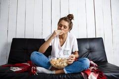 Piękny domowy dziewczyny łasowanie szczerbi się, dopatrywanie tv, siedzi przy kanapą zdjęcie stock