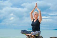 Piękny dorośleć starzejącej się kobiety robi joga na pustynnym tropikalnym beac fotografia royalty free