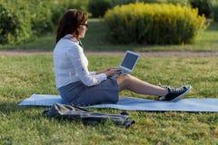 Piękny duży kobiety lying on the beach na zielonej trawie w parku z jej działaniem i laptopem Studencka dziewczyna patrzeje ekran fotografia royalty free