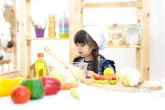 Piękny dzieciak dziewczyny kucharstwo i tnący warzywa Fotografia Royalty Free