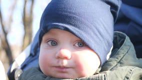 Piękny dziecko na spacerze je banana Dziecko z pięknymi niebieskich oczu spojrzeniami w kamera obiektyw zbiory wideo