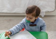 Piękny dziecko z pacyfikatorem maluje z kredkami na małym biurku obraz stock