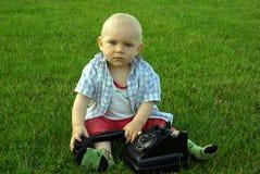 Piękny dziecko z telefonem na zielonej trawie obraz stock