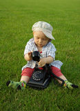 Piękny dziecko z telefonem na zielonej trawie fotografia royalty free