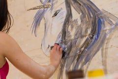 Piękny dziewczyna artysta maluje na ścianie jednorożec Zdjęcia Stock