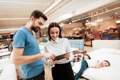 Piękny dziewczyna konsultant z ufnym mężczyzna robi out zakupowi materac w sklepie obrazy royalty free