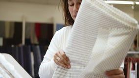 Piękny dziewczyna kupujący w tkanina sklepie Wybiera rolkę tkanina z polek kropkami wśród pasma światło zdjęcie wideo