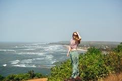 Piękny dziewczyna modniś relaksuje na dennych skałach fotografia royalty free