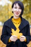Piękny dziewczyna portret z żółtym liściem w ręce, jesieni miasta park na tle, sezon jesienny Zdjęcie Royalty Free