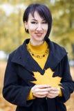 Piękny dziewczyna portret z żółtym liściem w ręce, jesieni miasta park na tle, sezon jesienny Obrazy Royalty Free
