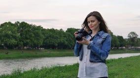 Piękny dziewczyna turysta bierze fotografie z fachową kamerą na bankach rzeka w wietrznej pogodzie zbiory wideo