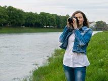 Piękny dziewczyna turysta w bawełnianej kurtce bierze fotografie z fachową kamerą na bankach rzeka w wietrznej pogodzie Obrazy Royalty Free