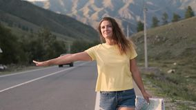 Piękny dziewczyna turysta zatrzymuje samochód z ręką podczas gdy chodzący na autostradzie z mapą w ręce zbiory wideo