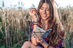 Piękny dziewczyna ucznia pole W jego ręce jest jabłko Pojęcie nowi pomysły, ono uśmiecha się, w lecie na naturze W ręce a Zdjęcie Royalty Free