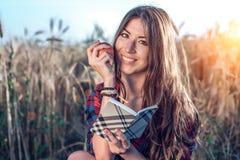 Piękny dziewczyna ucznia pole W jego ręce jest jabłko Pojęcie nowi pomysły, ono uśmiecha się, w lecie na naturze W ręce a Obrazy Royalty Free
