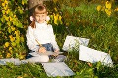 Piękny dziewczyny czytania list podczas gdy siedzący dalej Zdjęcia Stock