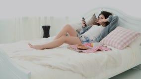 Piękny dziewczyny lying on the beach na łóżku w ranku i używać smartphone Młoda kobieta pisać na maszynie, wyszukujący internet i zdjęcie wideo