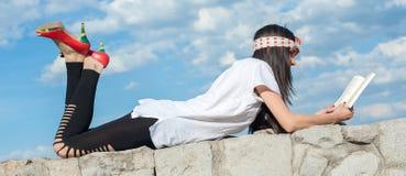 Piękny dziewczyny lying on the beach na ściennym i cieszyć się książkowego czytanie Zdjęcie Stock