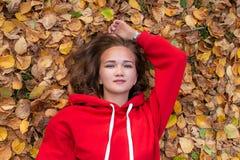 Piękny dziewczyny lying on the beach na jesień liściach w parku zdjęcie royalty free