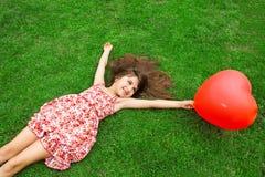 Piękny dziewczyny lying on the beach na mieniu i trawie czerwona piłka w Zdjęcie Stock