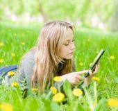 Piękny dziewczyny lying on the beach na trawie i używać pastylka komputer Zdjęcia Royalty Free