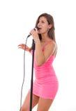 Piękny dziewczyny mienia mikrofon i śpiew w sukni Obrazy Royalty Free