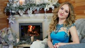 Piękny dziewczyny obsiadanie grabą w którym pali w domowej atmosferze i portrecie ogień potomstwa zbiory