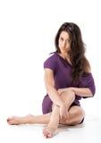 Piękny dziewczyny obsiadanie na podłogowym skrzyżowaniu ona nogi fotografia stock