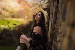 Piękny dziewczyny obsiadanie przeciw wiejskiemu krajobrazowi obraz stock