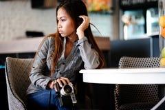 Piękny dziewczyny obsiadanie w barze z kamerą w ona ręki Obraz Royalty Free