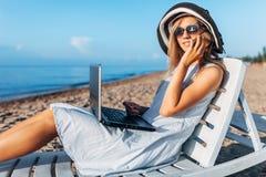 Piękny dziewczyny obsiadanie z laptopem na bryczki longue, kobieta pracuje na wakacje, akcydensowa rewizja, opowiada na telefonie zdjęcia royalty free