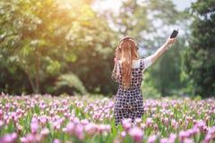 Piękny dziewczyny, technologii i czasu wolnego pojęcie, - dziewczyna kłama na natual i słuchaniu muzyka z hełmofonami obrazy royalty free