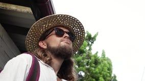 Piękny elegancki mężczyzna w słomianym kapeluszu i okularach przeciwsłonecznych stoi na ulicie zdjęcie wideo