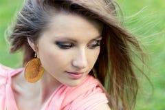 Piękny elegancki młodej dziewczyny obsiadanie w parku i wiatrze w twój włosy zdjęcia royalty free