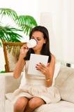 Piękny eleganckiej kobiety obsiadanie w kanapy używać Obraz Stock