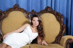 Piękny eleganckiej kobiety obsiadanie w karle fotografia stock