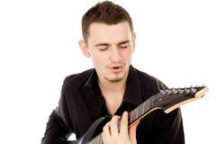 Piękny facet ubierający w czerni ubraniach śpiewa guita i bawić się Obraz Royalty Free