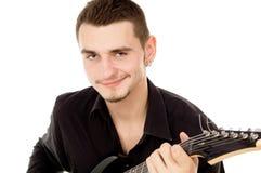 Piękny facet ubierający w czerni ubraniach siedzi gitarę i bawić się Fotografia Royalty Free