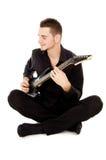 Piękny facet ubierający w czerni ubraniach siedzi gitarę i bawić się Obrazy Royalty Free