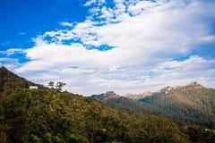 Piękny góra krajobraz z drzewami, chmurami i niebieskim niebem, Obrazy Royalty Free