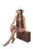 Piękny dziewczyny obsiadanie na starej walizce obraz stock