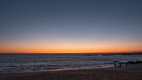 Piękny gradientowy niebo na plaży przy zmierzchem w Portugalia Sylwetkowi ludzie chodzi psa przy linią brzegową obrazy stock