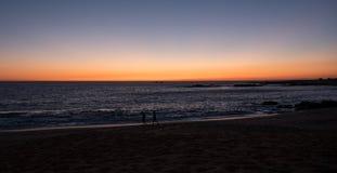 Piękny gradientowy niebo na plaży przy zmierzchem w Portugalia Sylwetkowi ludzie jogging wzdłuż linii brzegowej obraz royalty free