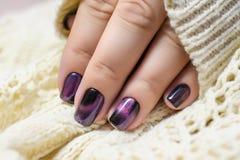 Piękny gwoździa połysk w ręce, purpura gwoździa sztuki manicure, biały tło Fotografia Stock
