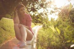 Piękny i atrakcyjny kobiety obsiadanie na stronie, jest ubranym seksownych przypadkowych drelichowych skróty Zdjęcia Stock