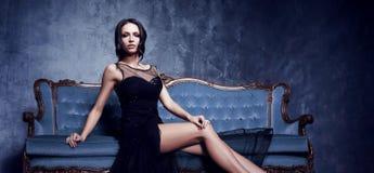 Piękny i młoda kobieto pozuje w czerni sukni na błękitnej kanapie vi Zdjęcie Stock