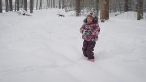 Piękny i rozochocony dziecko, biega szczęśliwie przez śniegu który tylko ostatnio spadał, Ona mała w posturze z, w ten sposób zbiory wideo