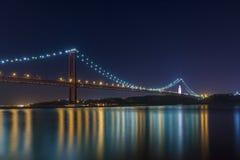 Piękny i spokojny widok Tagus rzeka i 25 Kwietnia most Ponte 25 De Abril przy nocą, w Lisbon Zdjęcie Stock