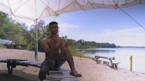 Piękny Indiański facet siedzi na ławce na jeziornym brzeg w szkłach chucha mydlanych bąble zbiory wideo