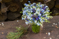 Piękny jaskrawy błękitny i biały bukiet z dzikimi kwiatami na drewnianym stole outdoors Zbliżenie fotografia Zdjęcie Stock
